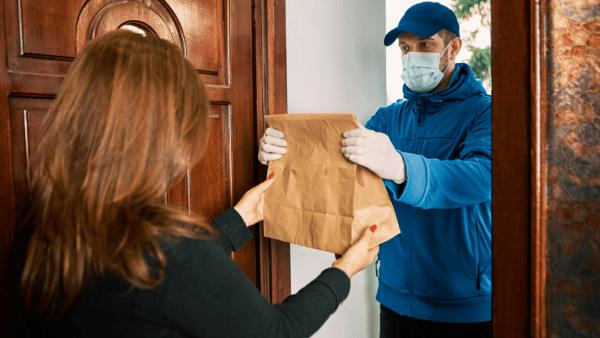 Repartidor entrega el paquete al cliente